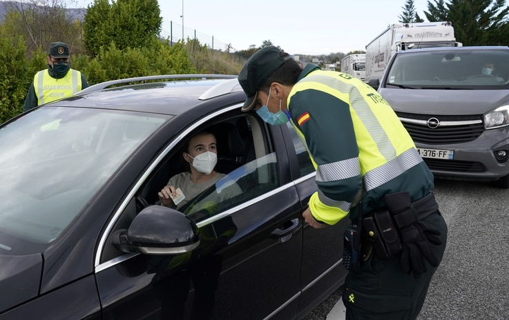 A Spanish Civil Guard questions a motorist after the Navarran local government limited all non-essential movement in and out of…