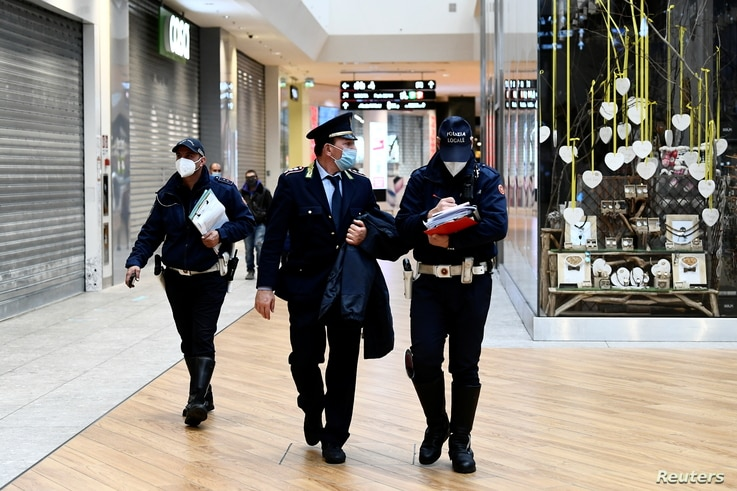 Local police officers check that stores are closed store in a partially closed shopping centre, after the Lombardy region…