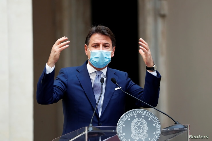 Italian Prime Minister Giuseppe Conte wearing a protective face mask gestures as he speaks during a news conference on…