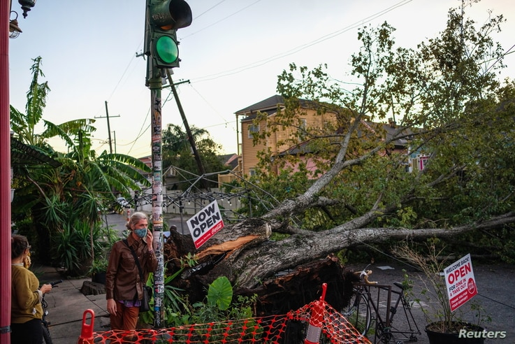 Olivia Mancing (L) and Zachery Quale talk outside of Flora Gallery and Coffee Shop near a downed tree in the street after…