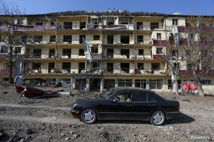 FILE PHOTO: A man drives a car past a damaged building following recent shelling in the town of Shushi (Shusha), in the course…