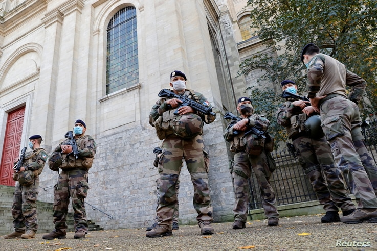 """French soldiers, part of France's national security alert system """"Sentinelle"""", patrol near the Cathedral in Arras."""