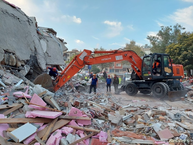 People search for survivors at a collapsed building after a strong earthquake struck the Aegean Sea town of Izmir.