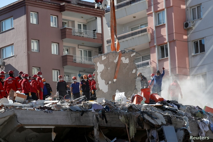 Rescue workers search for survivors at a collapsed building after an earthquake in the Aegean port city of Izmir, Turkey…
