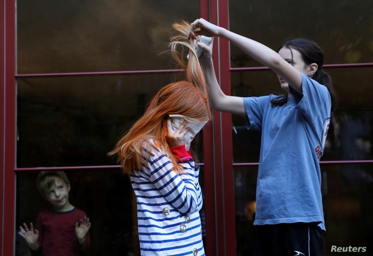 Jane Hassebroek helps her sister Lydia to dye her hair for a Chuckie costume for Halloween at their home, as the coronavirus…