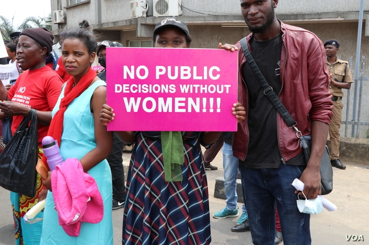 A protestor carries a sign during Friday's women rights demonstration in Malawi. (Lameck Masina/VOA)