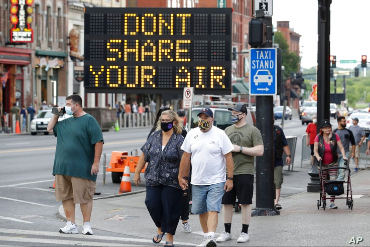 A sign encouraging the wearing of masks and keeping social distancing stands at a street corner Wednesday, Aug. 5, 2020, in…