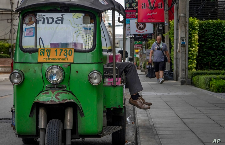 A tuk-tuk driver naps as a man walks past in an area, usually busy with tourists in Bangkok, Thailand, Thursday, Aug. 27, 2020…