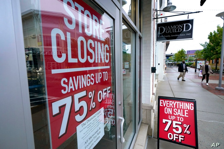 FILE - In this Sept. 2, 2020 file photo, pedestrians walk past a business storefront with store closing and sale signs in…