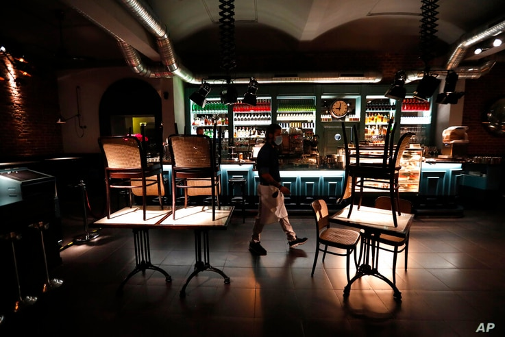 A staff member walks inside a closed bar in Prague, Czech Republic, Friday, Oct. 9, 2020. The Czech government has responded to…