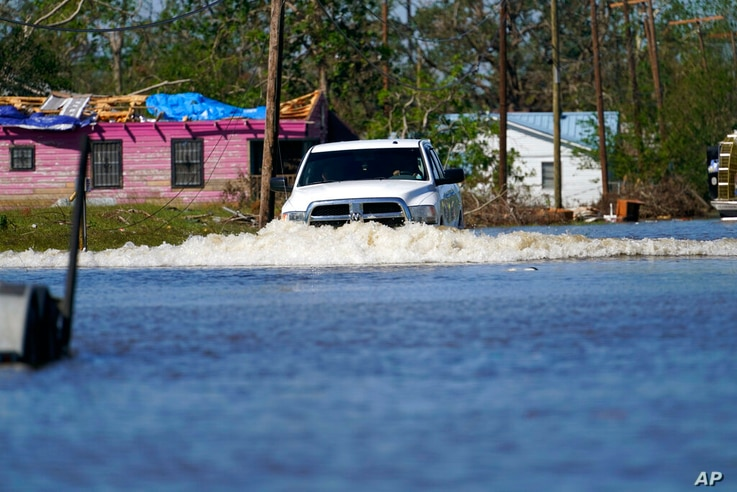 A truck drives through a flooded street in Lake Charles, La., Saturday, Oct. 10, 2020, past a home with damage from Hurricane…