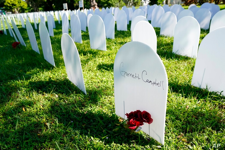 White plastic tombstone-shaped pieces are lined up as a temporary memorial to some of Miami's victims of the coronavirus at…
