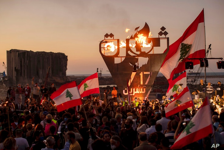 Anti-government protesters wave Lebanese national flags as they lit a giant flame over a metal statue that reads in Arabic: …