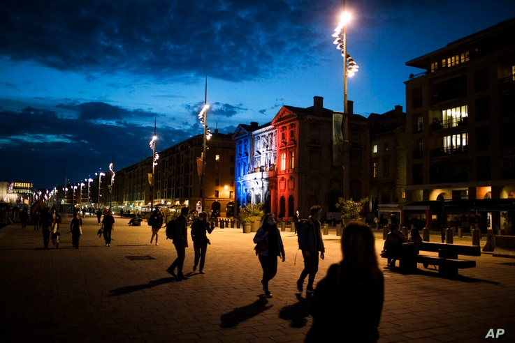 Pedestrians walk along Marseille's Old Port as the town hall is lit up in the French Tricolor to honor slain teacher Samuel…