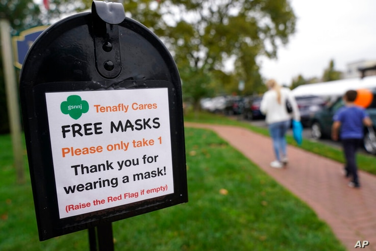 A mailbox containing free masks for pedestrians stands in the center of Tenafly, N.J., Thursday, Oct. 22, 2020. New Jersey's…