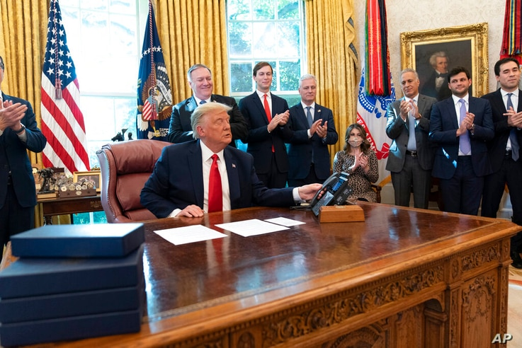 President Donald Trump hangs up a phone call with the leaders of Sudan and Israel, as Treasury Secretary Steven Mnuchin, left,...