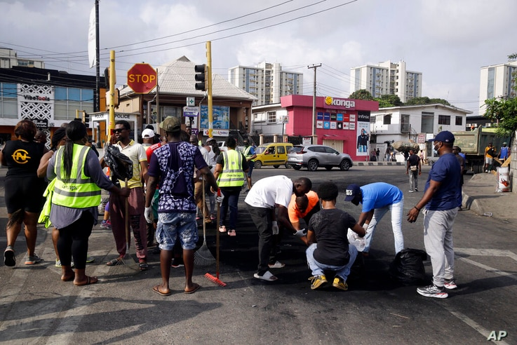Volunteers sweep burnt out tyres on the roads in Lagos Saturday, Oct. 24, 2020. Nigeria's president says 51 civilians have been…