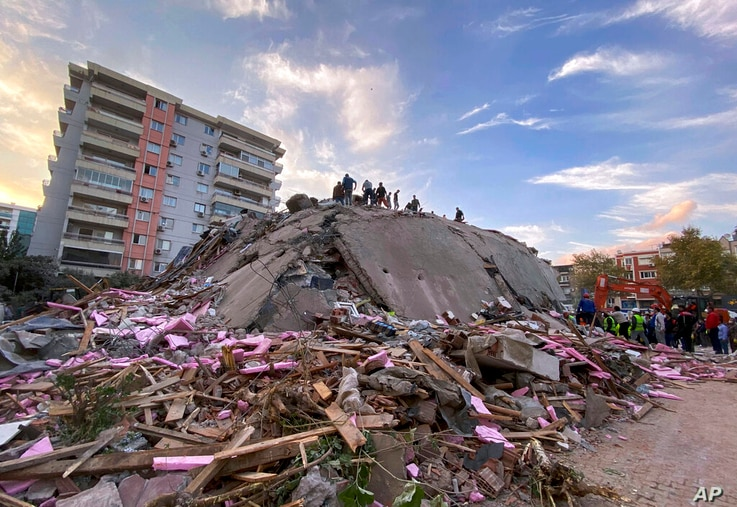 Rescue workers try to save people trapped in the debris of a collapsed building, in Izmir, Turkey, Friday, Oct. 30, 2020. A…