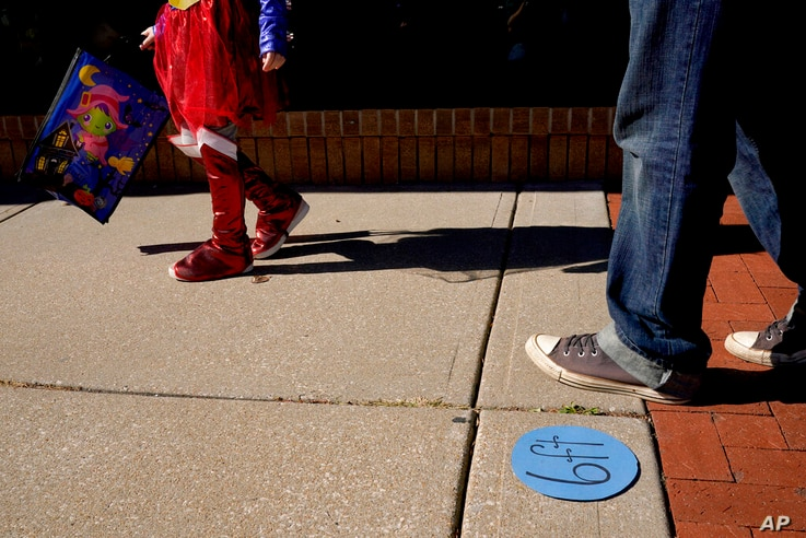 People walk past social distancing markers meant to help prevent the spread of the new coronavirus as they trick-or-treat for…