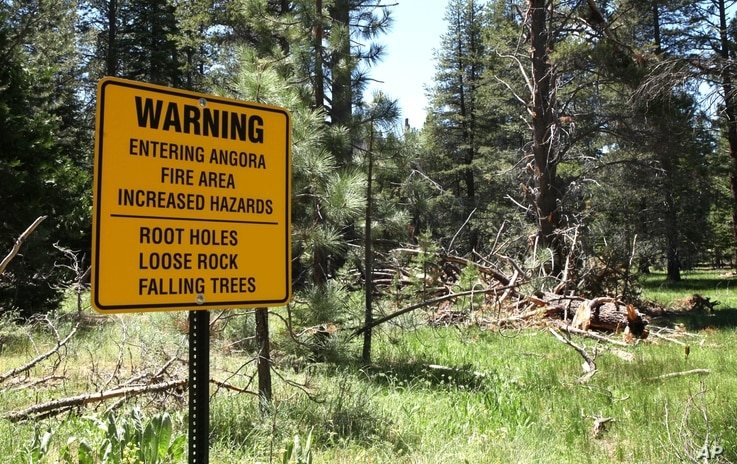 FILE -- In this July 6, 2010, file photo, a warning sign is seen for hikers entering the area burned  in the 2007 Angora Fire,…