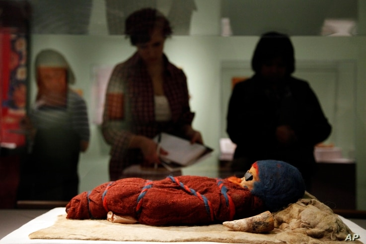 In a Feb. 18, 2011 photo, members of the media view an infant mummy discovered in the Tarim Basin in far western China, at the…