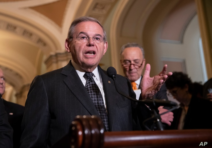 Sen. Bob Menendez, D-N.J., the ranking member of the Senate Foreign Relations Committee, joined at right by Senate Minority…
