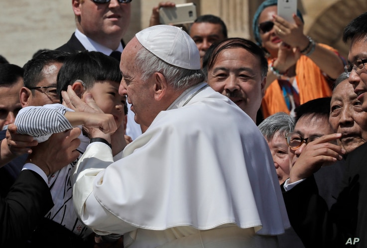 Pope Francis kisses a child with a group of faithful from Shanghai during his weekly general audience in St. Peter's square at…