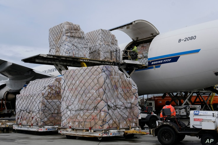FILE - In this April 10, 2020, file photo, ground crew at the Los Angeles International airport unload pallets of supplies of…
