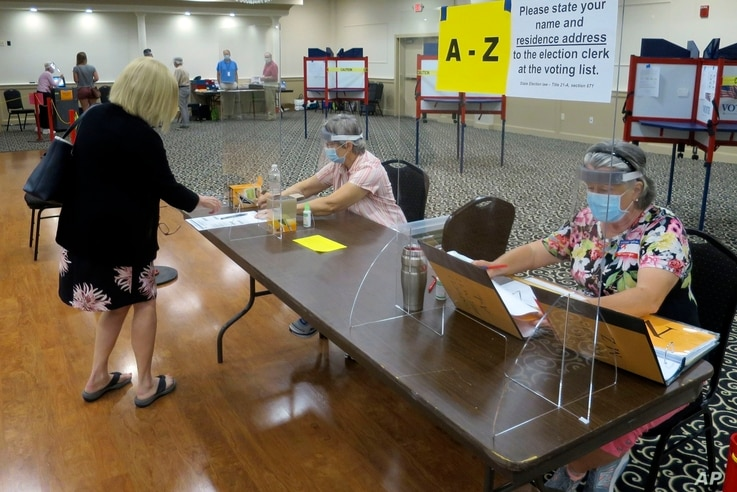 Election workers Adonlie DeRoche, seated left, and Judy Smith, seated right, assist voters during primary elections on July 14, 2020, in Portland, Maine.