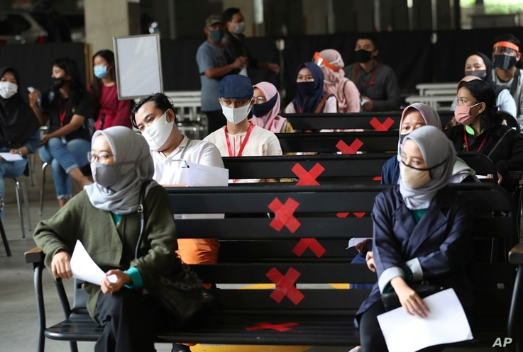 Employees working at AEON Shopping Mall sit spaced apart as they wait for their turn to take coronavirus test in Tangerang on…