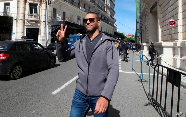 FILE - In this March 10, 2020 file photo, Algerian journalist Khaled Drareni flashes the V sign as he leaves the courthouse in…