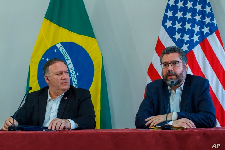 U.S. Secretary of State Mike Pompeo looks at Brazilian Foreign Minister Ernesto Araujo speaking during a press conference at…