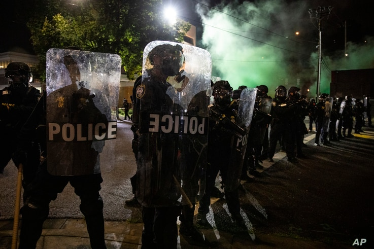Tear gas fills the air as police make a line of control during protests, Friday, Sept. 18, 2020, in Portland, Ore. The protests…