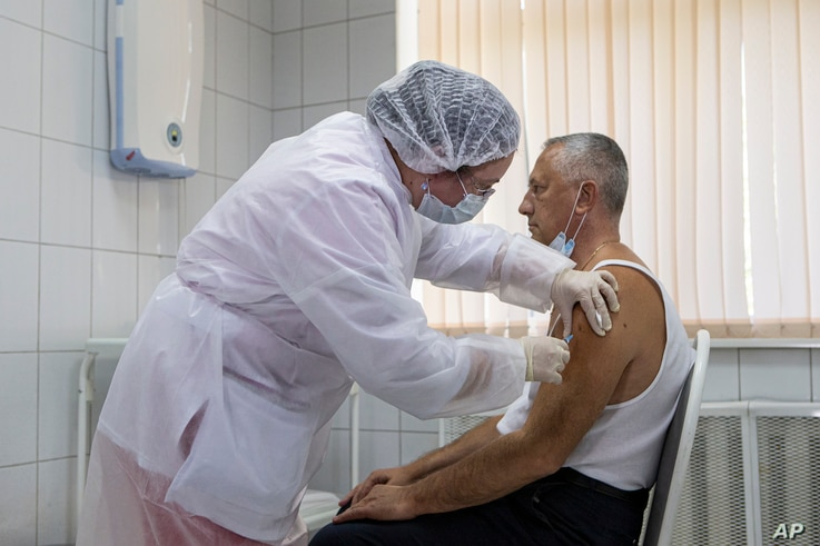 FILE - In this Tuesday, Sept. 15, 2020, file photo, a Russian medical worker administers a shot of Russia's experimental…