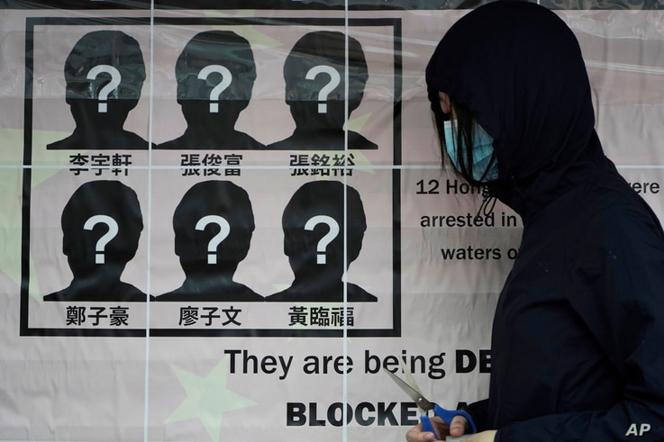 A university student puts up a poster to demand of releasing the 12 Hong Kong activists detained at sea by Chinese authorities,…
