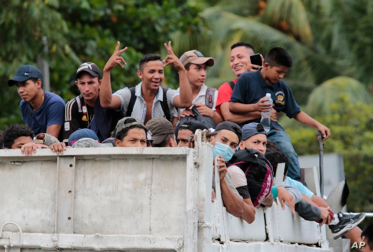 Migrants get a free ride from a trucker toward the Guatemalan border after leaving San Pedro Sula, Honduras, Thursday, Oct. 1,…