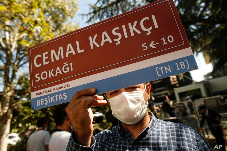 A man, holding an unofficial street sign reading in Turkish: 'Jamal Khashoggi Street', participates in an event near the Saudi Arabia consulate in Istanbul, marking the two-year anniversary of his death, Oct. 2, 2020.