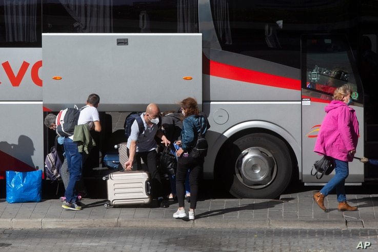 Passengers wearing masks to protect against coronavirus disembark from a coach at the main bus station a few hours before the…