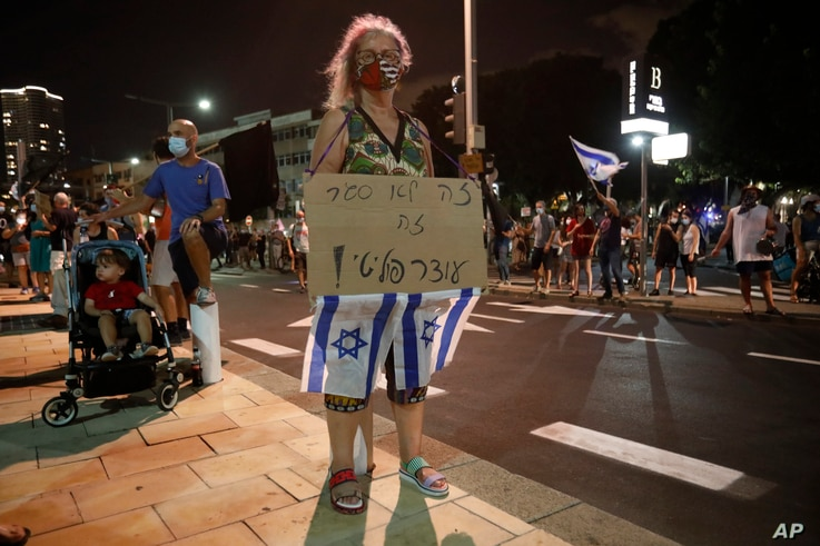 """An Israeli protester holds a banner saying """"it not a lockdown its a political curfew"""" during a demonstration against lockdown…"""