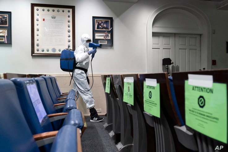 A member of the cleaning staff dressed in a protective suit, sprays the James Brady Briefing Room of the White House, Monday,…