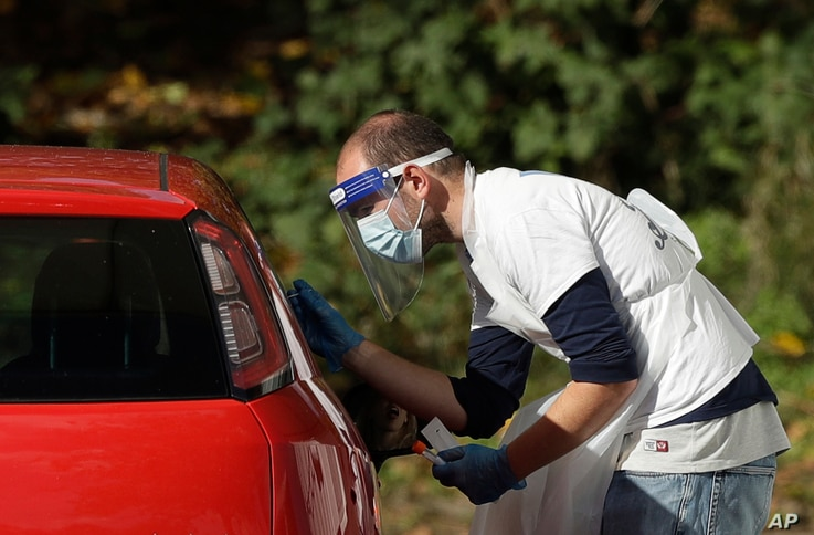 A person is tested for COVID-19 at a drive-through testing centre in a car park at Chessington World of Adventures, in…