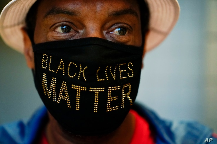"Calvin Stalling, of Atlanta wears a ""Black Lives Matter"" mask while he waits in a line to vote early at the State Farm Arena on…"