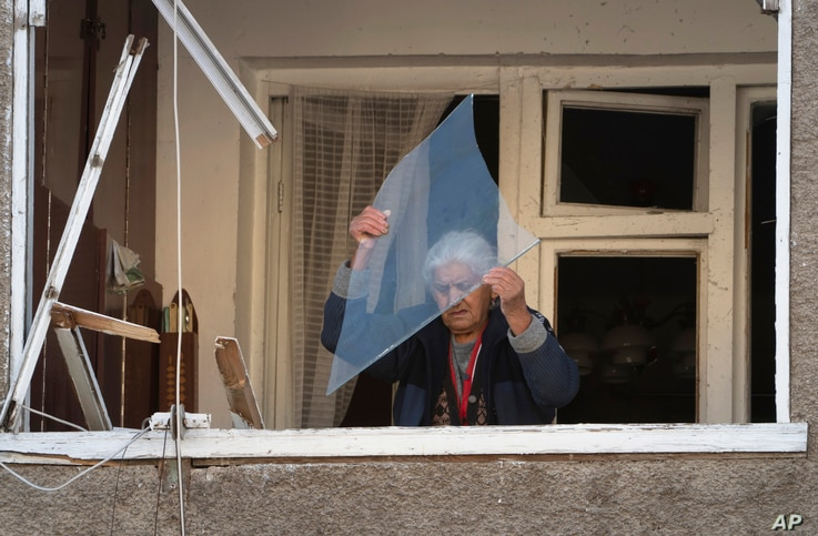 An elderly woman throws a piece of glass from her balcony in an apartment building damaged by shelling by Azerbaijan's artillery during a military conflict in Stepanakert, the separatist region of Nagorno-Karabakh, Oct. 12, 2020.