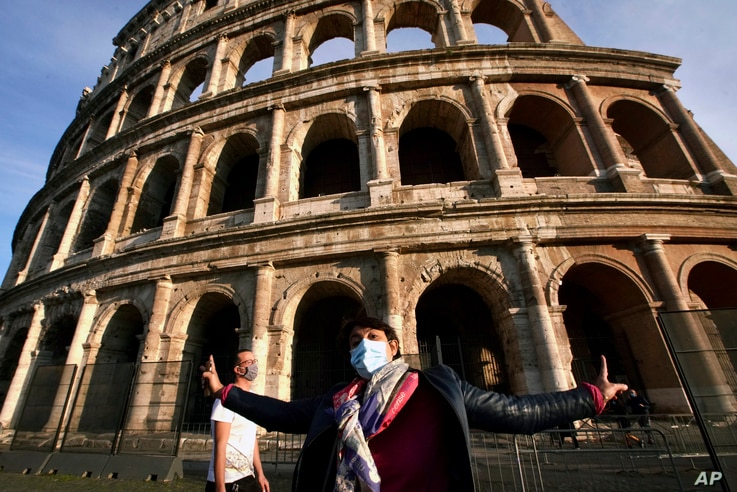 A tourist guide wearing a mask speaks in front of the ancient Colosseum in Rome, Oct. 13, 2020.