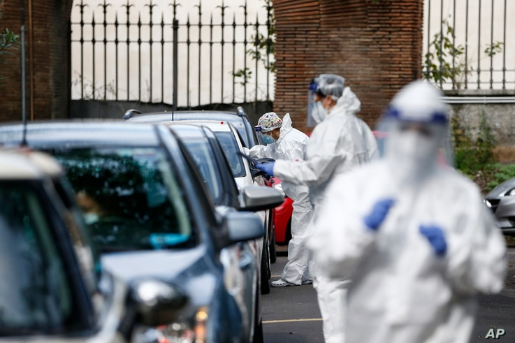 Medical staffers take swabs as they test for COVID-19 at a drive-through, in Rome, Tuesday, Oct. 13, 2020. Italian Premier…