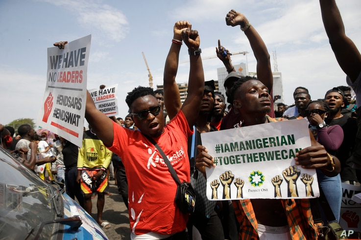 People hold banners as they demonstrate on the street to protest against police brutality in Lagos, Nigeria, Thursday Oct. 15,…