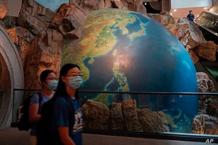 Visitors wearing masks to help protect against the coronavirus walk past an earth sculpture, at the Hong Kong Museum of History, in Hong Kong, Oct. 16, 2020.