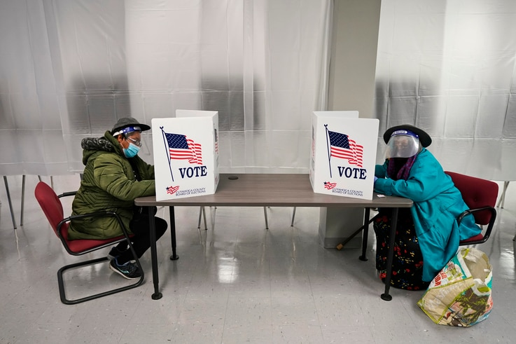 FILE - In this Oct. 6, 2020, file photo two voters fill out ballots during early voting at the Cuyahoga County Board of…