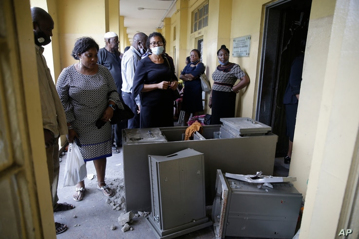 People inspect a damage safe at the federal high court building in Lagos, Nigeria, Oct. 26, 2020.