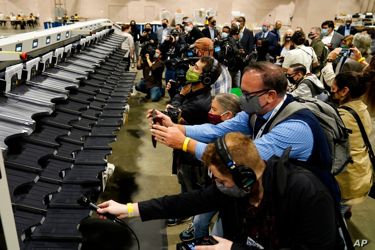 Media members photograph and record a sorting machine at Philadelphia's mail-in ballot sorting and counting center in…